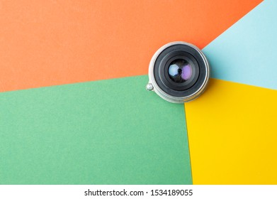 one small old photo lens on a colored background, digital color rendering concept, copy space