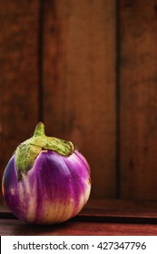 One small purple and white eggplant on wood background