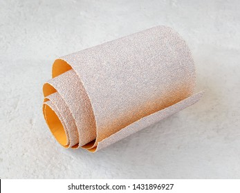 One small roll of extra coarse aluminum oxide sandpaper on a white rough textured background. Abrasive paper for dry sanding. Processing wood and metals, furniture production. Close-up.