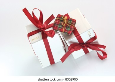 one small tiny gift box with two white gift boxes with red ribbon for valentines day and love gifts shopping concepts