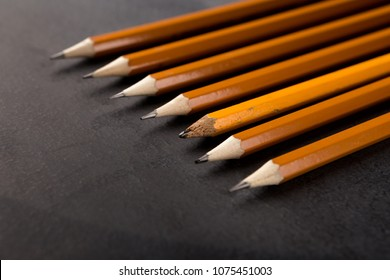 One small used pencil among plenty of new identical ones. Appearances are deceitful, uniqueness, think different, independence, leadership concept, copy space
