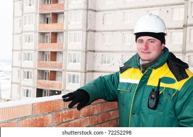 one smiley builder foreman at construction site in winter work wear and hard hat