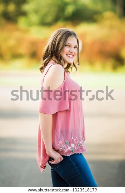 One Smiling Caucasian High School Senior Girl Outside during Summertime.