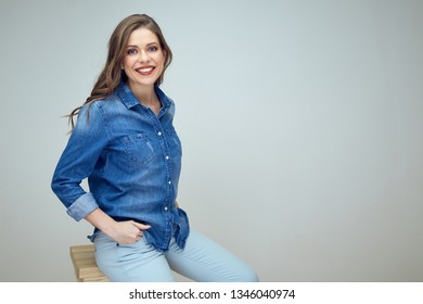 one smiling female model sitting on stool in photostudio. isolated portrait of girl in blue shirt.