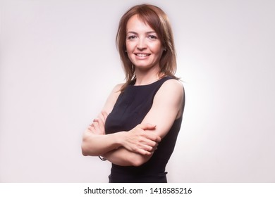 one smiling mature woman, 40-49 years old, good looking and beautiful portrait, with her arms crossed. Looking at camera. Upper body shot, wearing a simple black dress. Shot in studio on seamless gray