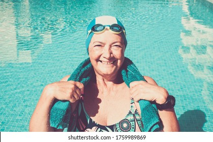 One smiling senior woman doing sport in the outdoor swimming pool under the sun. Blue swim cap and goggles. Healthy lifestyle of one retired people