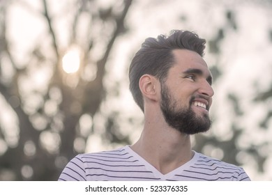 One smiling young adult man, looking sideways, head, face close up. Wearing t-shirt, outdoors nature. Low angle shot. Sun.