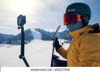 one snowboarder use action camera taking selfie on winter ski resort piste