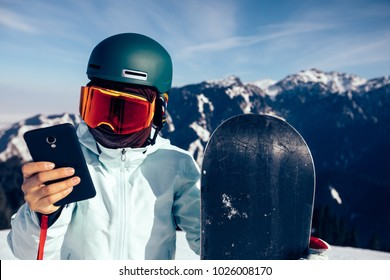 one snowboarder use smatphone on winter mountain top