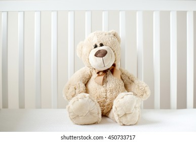 One soft bear toy at white children's bed.
