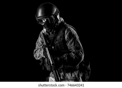 One soldier holding assault rifle. Uniform conforms to special services FSB of the Russian Federation. Shot in studio. Isolated with clipping path on black background (black and white)