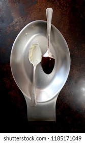 one spoonful of melted white chocolate, one spoonful of melted bittersweet chocolate resting on a metal spoonrest on dark background
