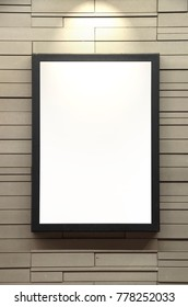 One spot light shining bright on blank space picture frame black border frame on brick wall