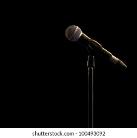 one standing microphone in a spot light.