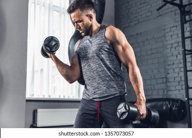 One step closer. The athlete trains in the gym, doing strength exercises for muscles, triceps and biceps, work on his upper body with weights and dumbbells. Fitness, healthy and self-control concept.
