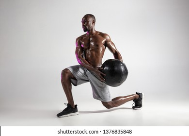 One step higher. Young african-american bodybuilder training over grey studio background. Muscular single male model in sportwear with the ball. Concept of sport, bodybuilding, healthy lifestyle.