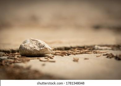 ein Stein einzeln auf der Straße mit unscharfem und farbigem Hintergrund, Steine und Hintergrund sind in hellbraunen Farben