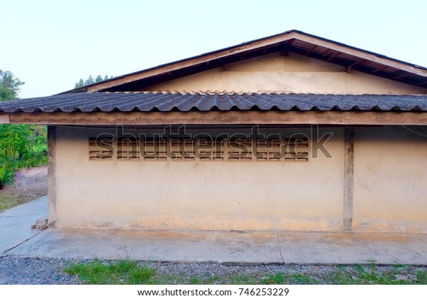 One storey house in the Thai countryside .The side has brick ventilation openings.