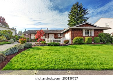 One story house with brick wall trim and clapboard siding. View of green front yard with white wooden fence