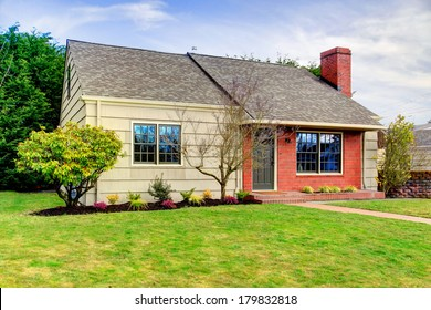 One story siding house with tile roof and brick trim. View of the front exterior , walk way and green lawn