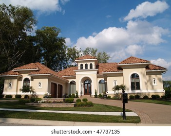 One story stucco residential home with a red clay tile roof and side garage.
