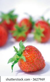 One strawberry in focus with others in the background