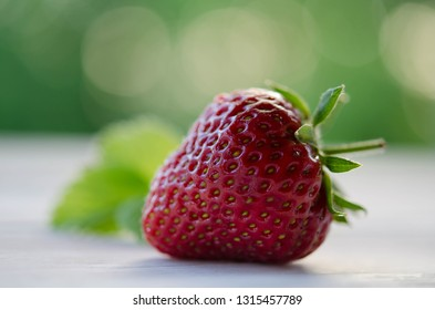 one strawberry on a wooden table
