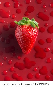 One strawberry over red background with water drops