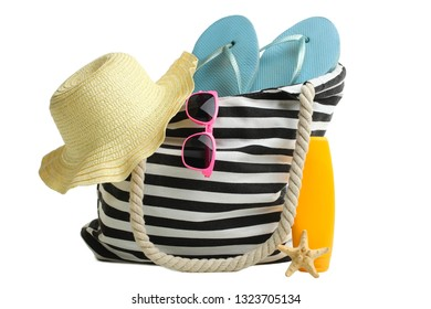 One striped beach bag with different beach accessories isolated on white. Concept summer, vacation on the beach.