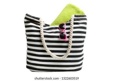 One striped beach bag with green towel and sunglasses isolated on white.  Concept summer, vacation on the beach.