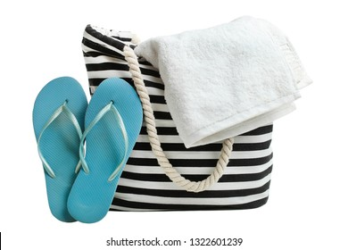 One striped beach bag with white bath  towel and blue rubber slaps isolated on white. Concept summer, vacation on the beach.
