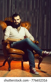 One stylish fashionable handsome brunette man with long lush beautiful beard in grey shirt and blue jeans sitting on brown leather retro chair looking forward indoor on studio background, vertical pic
