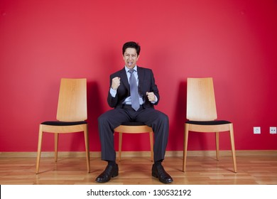 One successful businessman between two empty chairs