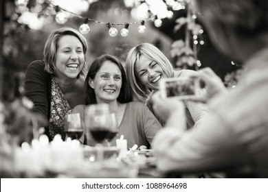 One summer evening friends gathered around a table in the garden for a good time. A man takes a picture of three female friends in their forties.Black and white