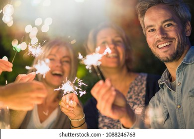 One summer evening, looking at camera, friends in their forties gathered around a table in the garden. They have fun while burn sticks of sparks.
