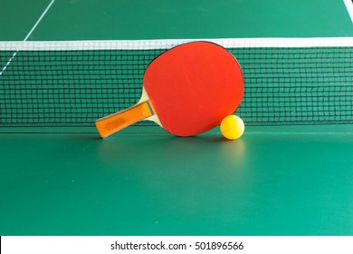 one  table tennis or ping pong red  rackets and yellow  balls on a green table with net