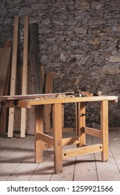 One table with wood beam and multiple assorted tools on top of it with plank floor in front of rock wall