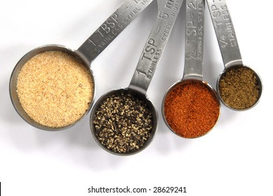 One Tablespoon, One Teaspoon, Half Teaspoon and Quarter Teaspoon measuring spoons filled with colorful spices isolated on a white background.