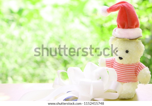 One teddy bear wear red Christmas cap with white bow on blur green bokeh background have copy space