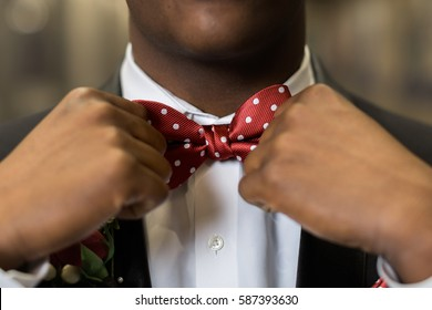 One teen boy adjusts polka dotted red bow tie. Getting dressed and ready for formal high school prom dance.
