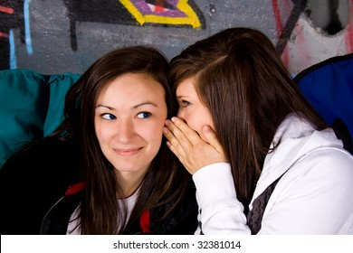 One Teenage Whisper Something into the Ear of her Friend