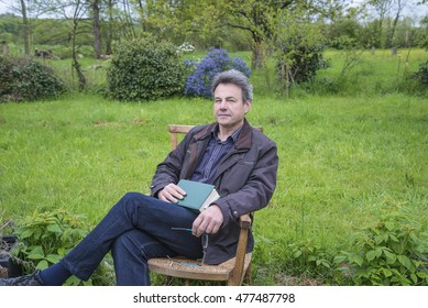One thoughtful mature european man with a book in a chair outdoors