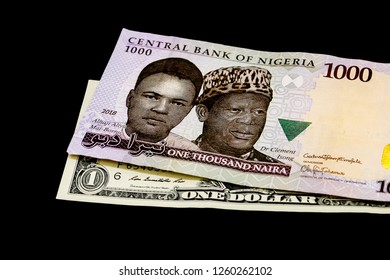 One thousand Nigerian Naira and US Dollar banknotes, isolated on a black background. Foreign exchange, global finance, African trade. Nigerian and American money.