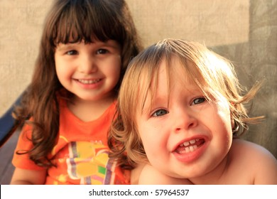 One and three year old girls sitting and smiling