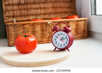 One tomato and red clock on retro box background