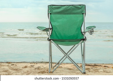One tourist chair stands on the shore on the background sea horizon. Back view. Сoncept of meditation and calm