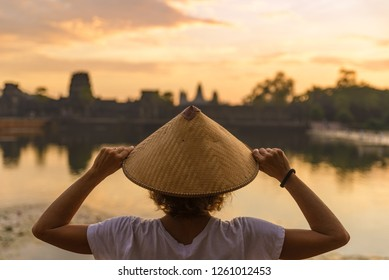 One tourist visiting Angkor Wat ruins at sunrise, , travel destination Cambodia. Reflection on water pond amid jungle, woman with traditional hat, rear view.