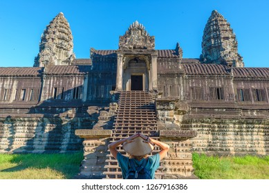 One tourist visiting Angkor Wat ruins at sunrise, travel destination Cambodia. Woman with traditional hat and raised arms, rear view, main facade staircase gate and towers.