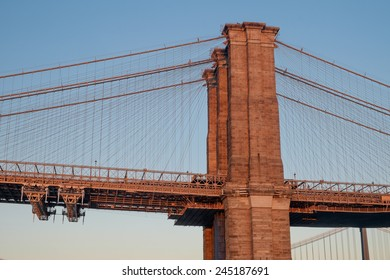 One of the towers of the famous old and historic Brooklyn Bridge spanning the East River from Manhattan into Brooklyn as seen at sunset