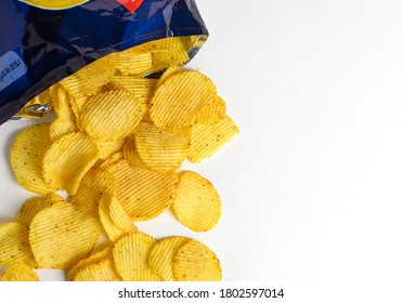 one of the types of snacks, fast food, junk food - ruffled potato chips spilling out of an open bag on a white background